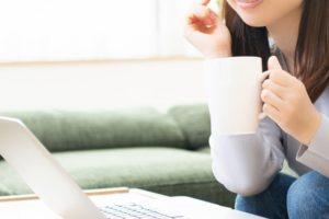 パソコンの前でコーヒーを持っている女性