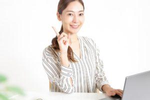 パソコンの前で人差し指をあげる女性
