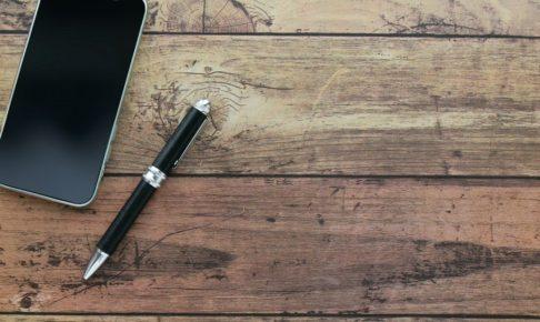 机の上のスマホとペン