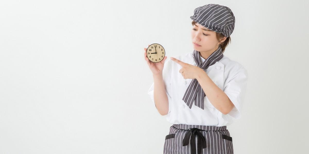 時計を指差す女性